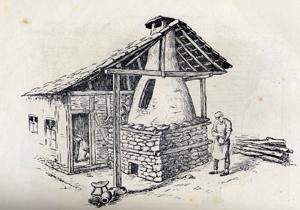 Оригинална конусообразна затворена грънчарска пещ с работника до нея